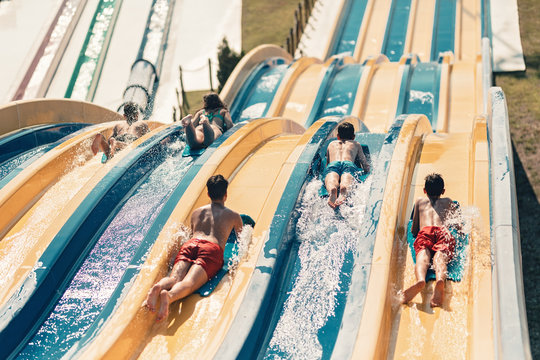 Young people having fun on the water slide with friends and familiy in the aqua fun park glides, happy falling into water and water splashes are all over. Blue sky background looks amazing sunlight