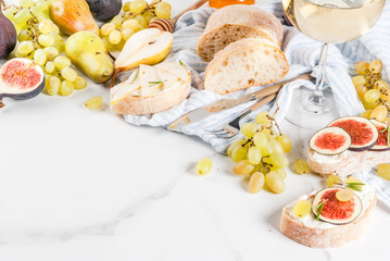 Sandwiches with ricotta or cream cheese, ciabatta, fresh figs, pears, grape, walnuts and honey on white marble table table, with wine glass copy space