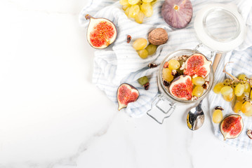 Autumn breakfast ideas, recipes. Jar of overnight autumn oats with red figs, grapes and walnuts. On white marble table, copy space