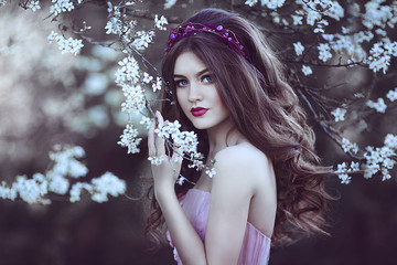 Beautiful Romantic Girl with long hair in pink dress near flowering tree.