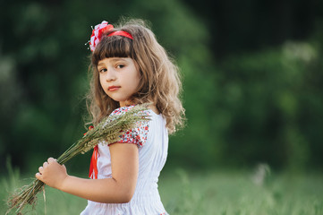 Little beautiful girl walks in the forest and collects field plants. Spring.