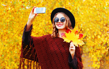 Autumn fashion smiling young woman taking a picture self portrait on the smartphone in knitted poncho