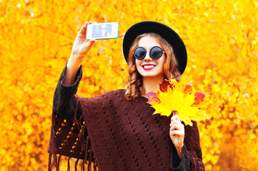 Autumn fashion smiling young woman taking a picture self portrait on the smartphone, wearing a knitted poncho