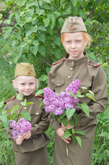 Portrait of two girls in uniform. Children with lilac flowers