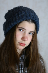 teenager girl close up portrait in knitted winter blue hat