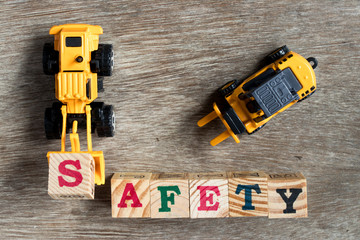 Toy plastic bulldozer hold toy block letter s to fulfill word safety with forklift on wood background