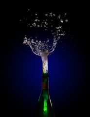 champagne bottle explosion with cork popping splash against a dark background with blue to black gradient, copy space