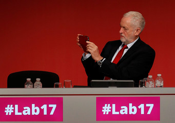 Britain's opposition Labour Party leader Jeremy Corbyn takes a picture during Shadow Chancellor John McDonnell's speech at the Labour Party Conference in Brighton