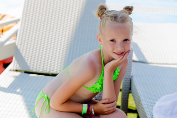 Young girl in a swimsuit on a shelf by the pool