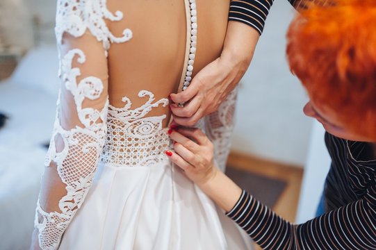 The mother helps the bride to fasten her corset on the wedding lace dress.