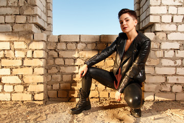 Young girl dressed in leather clothing, posing in abandoned building