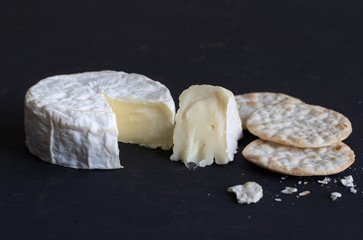 Camembert soft creamy cheese and crackers on black background - Space for text