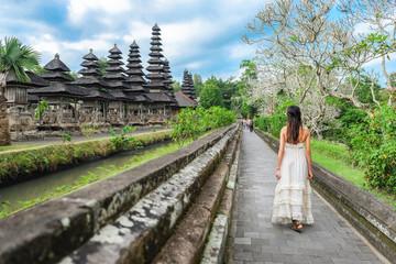 Asian girl walking in Pura Taman Ayun Temple in Bali, Indonesia.