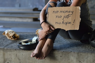 a homeless punk woman begging, holding a sign - no money no job no hope