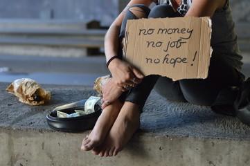 a homeless punk woman begging, holding a sign - no money no job no hope