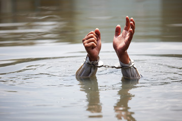 businessman was arrested by handcuffs and drowning in water with copyspace.