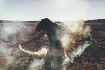 A rebellious, youthful man plays with fireworks in the desert