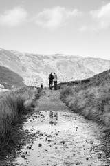 Young couple walking on a mountain path. Cumbria, UK.
