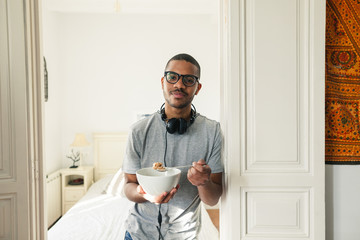 Latin man in bedroom holding a cereal bowl.