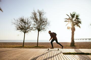 Man riding on longboard on beach promenade.