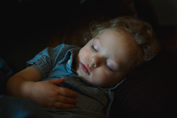 young boy sleeping on couch