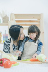 Mother preparing food and teaching her daughter cooking food in the kitchen at home, healthy food