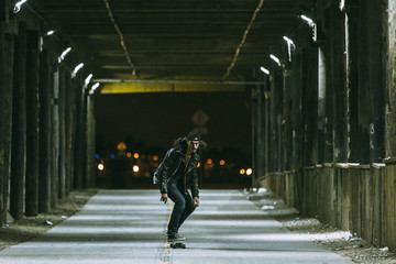 A young skateboarder travels through a tunnel under the Santa Monica Pier