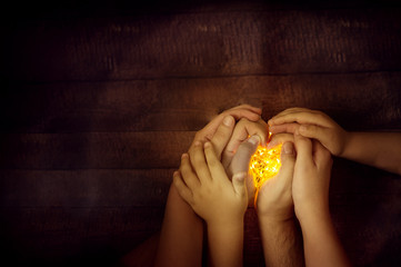 christmas mood top view family hands holding lights: mom, dad and kid. wooden background