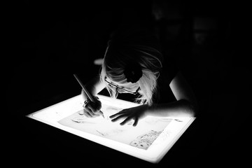 Black and white of girl using a light-box to trace a picture.