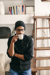 Portrait of a latin man drinking a cup of coffee at home.