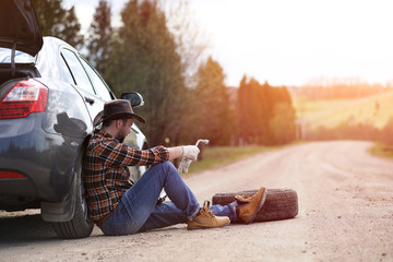 Man is sitting on the road by the car
