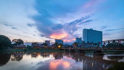 The historical iron bridge at Chiangmai city skyline at Ping river at dusk. Chiangmai , Thaland. Long exposure photograph.