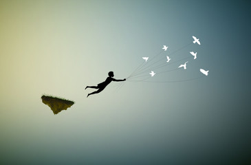 Fototapeta boy is flying away and holding pigeons, fly in the dream land,fly away, shadows, obraz
