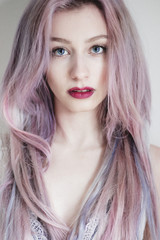 Portrait of a beautiful young woman with blue eyes and pink hair