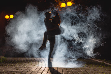 The man lifting a woman on the street with a smoke. night time