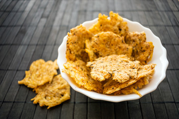 Cheese Chips Snack in a round white bowl on a black wooden background. Grain Free Dippable Crispy Cheese Chips, Keto & Low Carb. Crunchy chip to snack from cheddar, parmesan, herbs, spices