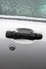 Car door covered in glaze ice