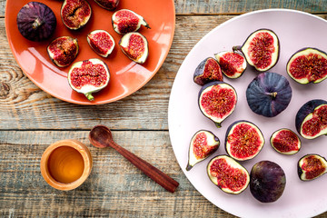 Plate of fresh blue figs on wooden background top view