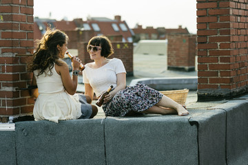 Female couple on city rooftop