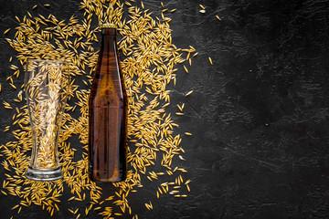 Grains of malting barley near beer bottle on black background top view copyspace