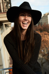 Young woman in black hat laughing on balcony