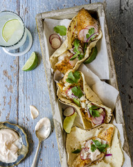Close-up of homemade delicious grilled fish tacos, sauce and mojito