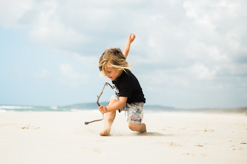 child running and playing with driftwood on an empty beach