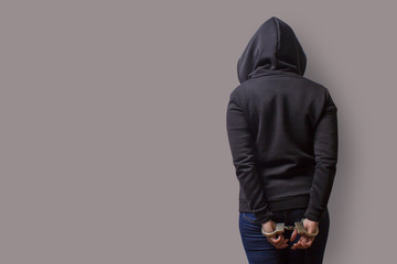 rear view of a girl in a black hood with handcuffed hands isolated on a gray background
