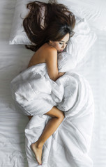 Dreamy asian female covered with white bed sheet /look from above