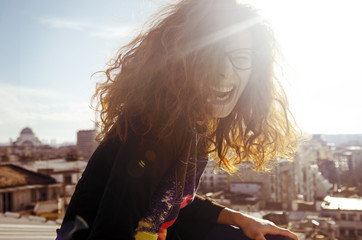 Redhead girl dancing and laughing on the rooftop