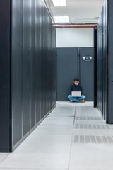 Female engineer using laptop in data center