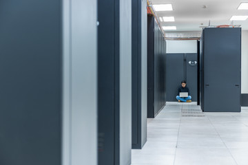Female technician using a laptop while sitting in data center