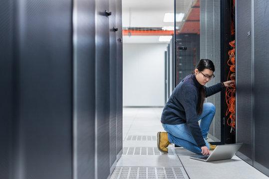 Female technician working on server in data center