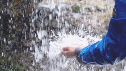man refreshing his hands in stream of water of natural waterfall